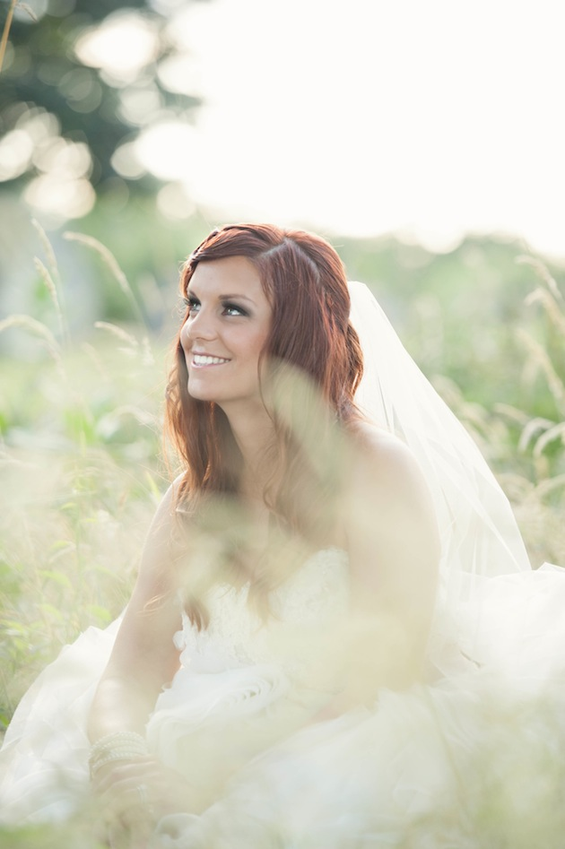 bride sitting in field