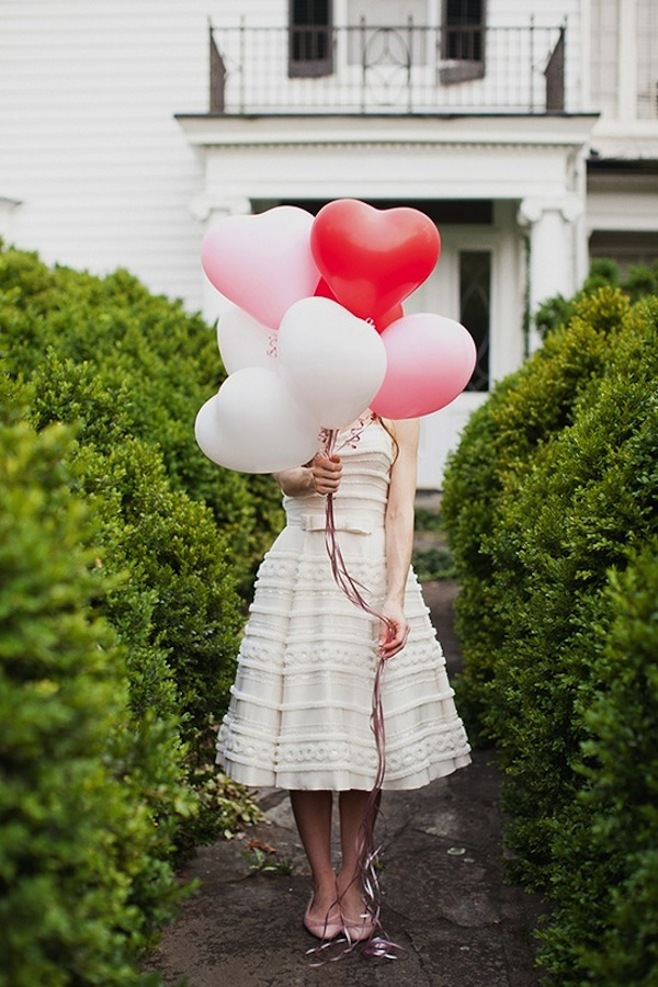 Bride carrying heart balloons