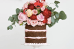 nake wedding cake topped with red and pink florals